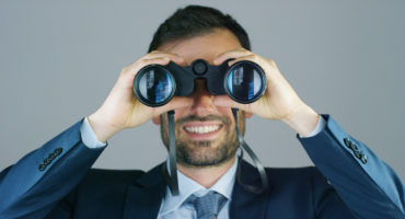 A businessman in a suit and tie, use the binoculars to look away with the concept of looking to the future, forecasting the economic and financial growth and the future
