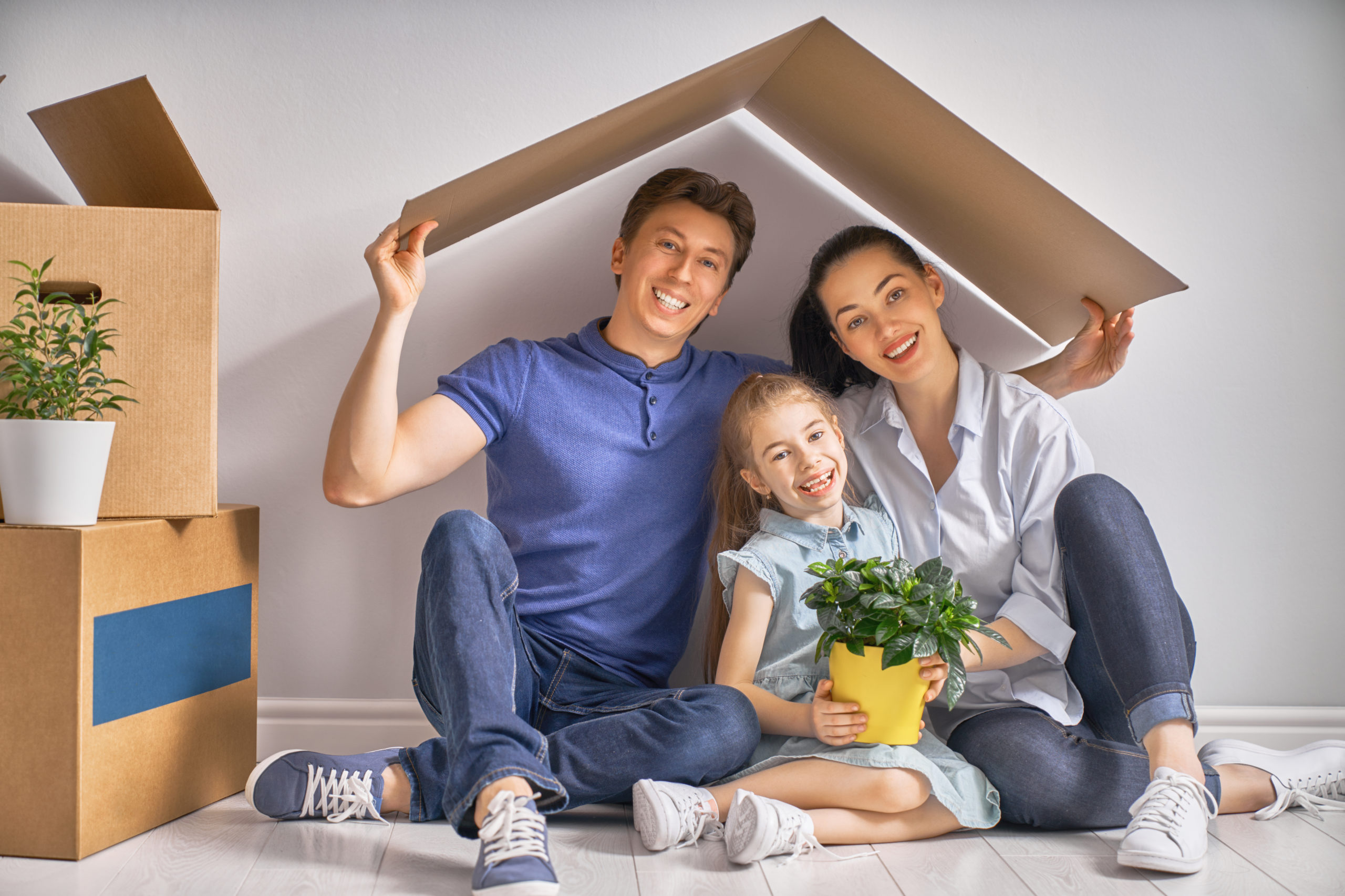 Mother, father and child girl in the house with a symbol of roof. Concept of housing for young family.